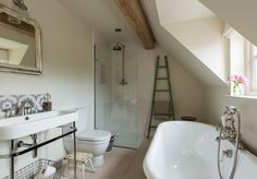 Contemporary traditional bathroom with roll top bath and frameless shower. Bert and May tiles www.borderoak.com