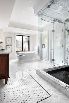 White bathroom with marble bathroom flooring, glass shower and standalone tub.