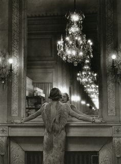 A model pauses to regard herself in the grand mirror of the Molyneux atelier, Paris, 1934. Photo by Alfred Eisenstaedt