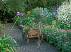 Antique wheelbarrow full of garden waste, spade and fork against a colorful wheelbarrow!
