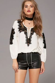A silk top featuring a self-tie lace-up front, semi-sheer floral lace panels, split neckline, long sleeves, and an elasticized waist.