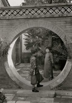 Two young Chinese girls chat with each other in a moon gate in a courtyard of a Chinese home, 1932.Photograph by W. Robert Moore, National Geographic