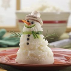With Mashed Potatoes Use an ice cream scoop to form the body of the snowman Use 2 peppercorns for the eyes and 3 peppercorns for the buttons Use an upside-down mushroom for the hat Tie a green onion for the scarf Use two rosemary leafs for arms Use a small sliver of carrot for the nose Use cucumber shavings for the mouth
