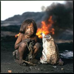 Poor child - I don't know where, but I do know it breaks my heart. Homeless kic, fire, powerful face, strong image, intense eyes, Oh Dear, poverty, dispair, pain, hurt, portrait, photo
