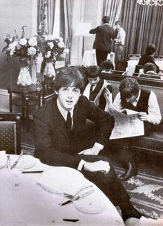 Beatles replacement drummer JIMMY NICHOLS fake-reading a newspaper with John while Paul smiles for the camera