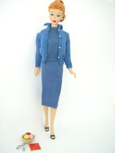 Long winter nights are spent 'Knitting Pretty' for Barbie in 1963. Barbie wears her original 'Sweater Girl' outfit from 1959, but in a new colourway, Royal Blue. It's so smart and co-ordinated. Barbie wears a Royal blue real wool knitted 'shell', cardigan sweater, and wool flannel sheath skirt. Black open toe shoes, wooden bowl with three balls of wool, a set of silver knitting needles, 'real' working silver scissors, and her 'Learn To Knit' 'Book'. A lovey outfit, and a very popular one…