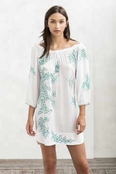 With its wide neckline, the White Aba Dress Tunic creates a stunning bohemian look. The entire dress is covered in geometric turquoise embroidery that highlights the elegance of this beautiful piece. An elasticized rope securely holds the dress in place. Wear it with sandals and a beautiful necklace for an alluring off-shoulder look.