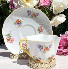 Vintage English Shelley Dainty Tulip Bouquet Tea Cup. This pattern was made by Shelley China from 1945 to 1966 and features a delicate pattern of Pink Roses, Purple Tulips, other garden flowers.