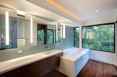 A sleek, modern bathroom tucks into one side of this mid-century master bedroom retreat, with no walls to divide it from the main space. The white shower is completely enclosed by glass, visually expanding the space. A floating vanity continues the minimal, modern theme.
