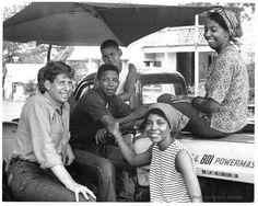 Local teenager Doug Smith (AssistDir,Youth Coordinator Hattiesburg project) sits behind the wheel of one of Vernon Dahmer's tractors. Immediately behind him is Mr. Dahmer's son Dennis and to Dennis' right is his friend Alfonso Harris. Sitting on the tractor engine is Freedom School teacher Denise Jackson (Detroit, Michigan; a student at Barnard College), and standing beside the tractor is Lorne Cress (Chicago, Illinois), Dir CommCtrs . Vernon Dahmer's fish fry at the Kelly Settlement on July…