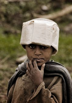 Africa | Portrait of a Tigray Child, Ethiopia. | © Tenbult on DeviantArt.   The hat is a plastic waste bag which he can fold to a raincoat if it happens to rain. After the rain he can fold it back together to make a nice little hat.