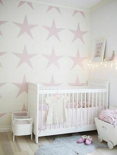 weißes Babybett und rose Sternen an der Wand