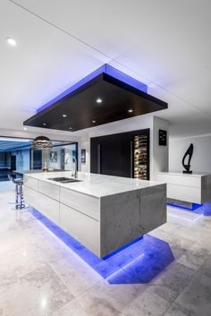 Featuring blue lighting that rings the ceiling and cabinets, it almost feels like you're looking at a set from Blade Runner. A focus on lighting – Kitchen by designer Kim Duffin