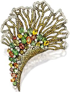 Fan-shaped brooch of openwork design, set with graduated sapphires of brown and yellow hues, edged by brilliant-cut diamonds, embellished to the center with clusters of oval sapphires of green, yellow, and brownish hues, highlighted by brilliant-cut diamonds, the sapphires and diamonds together weighing approximately 13.00 and 8.00 carats.