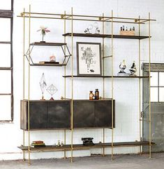 """3 Bay System with Credenza  (As Shown) Shelves: 6'-6"""" and 10' shelves, with Knife Edge Detail, in a staggered configuration. Strap Shelves: Hanging and Posting Versions Credenza: Two - 42"""" Wide Credenzas with patinated Sliding Doors Finish: Shelves and Credenza in oxidized Oak, Framework in solid brass with a warm finish Bay Widths: (Center to Center) 36"""" Size: 10' W x 22"""" D x 10'-6"""" High:"""