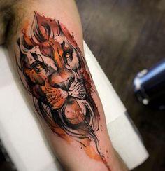 Tatuagem de leão inspirada no estilo aquarela, com cores vibrantes e marcantes