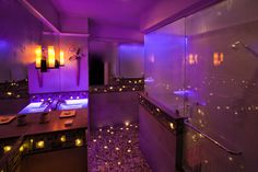 """The Thomas Wolfe bathroom features a """"roman bath"""" with water recirculating over your shoulders and a ceiling mounted four quadrant shower. Fiber optic lighting twinkles in the floor and walls and the LED lighting offers 64 separate color variations. This is our """"Purple Rain""""."""