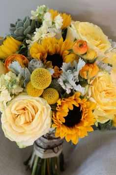A yellow wedding bouquet with sunflowers, roses, billy balls, succulents and dusty miller - the muted hues are ideal for a bride with vintage style.