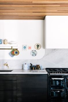 White Walls & Counter, Black Cabinets, Colorful Potholders, Gold Faucet, Polka Dot Cookie Jar // interesting
