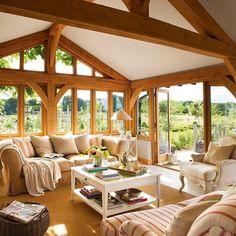 Salón con vigas de madera y ventanales al jardín