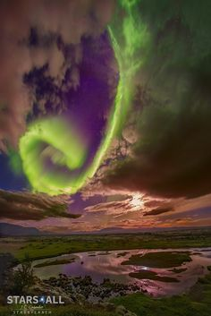 Aurora over Icelandic Fault | Admire the beauty but fear the beast. The beauty is the aurora overhead, here taking the form of great green spiral, seen between picturesque clouds with the bright Moon to the side and stars in the background. The beast is the wave of charged particles that creates the aurora but might, one day, impair civilization.