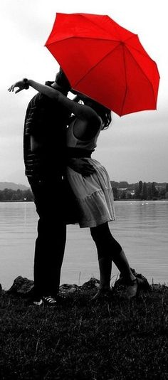 Black and white couple with red umbrella kissing