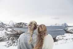 Two blond girls with braided hair in snowy Norwegian landscape