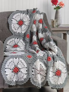 """The unique color combination on this design makes each motif pop. Made using 3 colors of Encore #4 worsted-weight yarn by Plymouth Yarn. Model is made using 6 skeins each white and quarry and 1 skein coral. Finished measurements 48""""W x 60""""L..."""