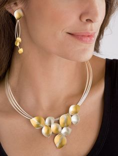 Dangling Leaves & Lotus Necklace by Judith Neugebauer. Shapely petals of sterling silver are splashed with 23k gold, creating lyrical adornments with elegant flowing beauty. Pendant is 2.5