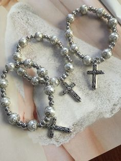 10 bracelets, favors religious favors perfect for Baptism, weddings, communions and anniversary,  or quincianeras favors.  Stretchy bracelet is made with glass pearls beads and metal beads included the metal cross.     in this section here is more items and more options BOX and ROSARIES favors OR OTHER FAVORS https://www.etsy.com/shop/NARELO?section_id=15500209&ref=shopsection_leftnav_3  SET ROSARIES WITH BAGS AND TAGS…