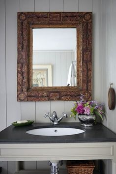 The bathroom's antique, straw-work frame mirror contrasts with an Oka 'Manor Bathroom Vanity Unit' painted in Farrow & Ball's 'Light Gray'