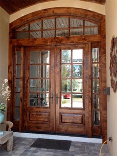 This custom entry has won awards & has been the inspiration for many other entry projects tbat we've done over the years. It is a double 8' tall Knotty Alder door with true divided, beveled glass with matching sidelites & transom. Complete with multi point locking system & Emtek hardware