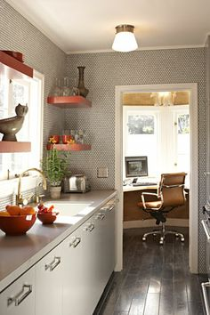 I really do like the simplicity of this small kitchen and the work space surrounded by windows.   The accents of orange, the wallpaper, floor and neutral grays with stainless are classic and stylized.