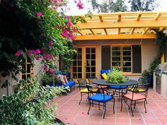 Paint a pergola and other architectural elements a bright color. Add coordinating Spanish tile to one wall to bring everything together. Design by Joan Grabel.