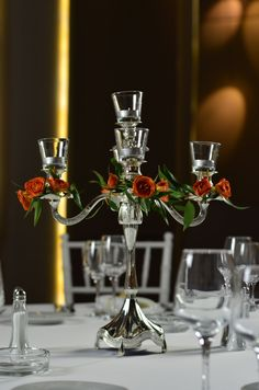 Delicate and vibrant orange tearose on a silver candle holder