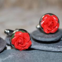 Welcome to Musa Natura, a place where you will find lots of handmade pieces inspired by Nature. Each one lovingly crafted by hand and made to order.  This listing is for a beautiful pair of Red Rose Cuff links.  The Roses have been hand sculpted from Polymer Clay and set onto a Silver Tone Cuff link Base.  It is sized at 1.2 cm across. Your Cufflinks will arrive presented in a little organza drawstring bag, wrapped in tissue paper.  My dispatch time is up to 5 working days as each item is…