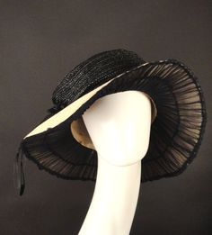 Fabulous c.1912 hat in ivory and black straw. The straw has a bubble crown and a floppy wide brim. Black silk horsehair is braided and tied into bows with tails trailing off the sides and ending in bl