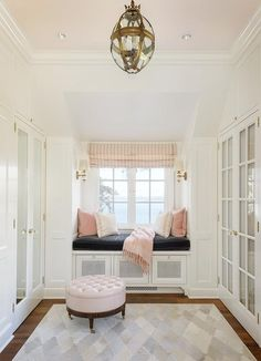White and pink walk in closet features a pink painted cieling accented with a glass and brass pendant light illuminating a round pink leather tufted storage ottoman on caster legs placed atop a hide quatrefoil rug facing mirrored wardrobe cabinet doors, Chic closet boasts a built-in window seat lined with a black velvet cushion and blush pink velvet pillows placed under windows dressed in pink striped roman shades lit by Jonathan Sconces and a Crown Top Banded Globe.