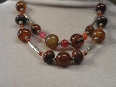 This designer holistic necklace is made of genuine Agate, Carnelian and Brecchiated Jasper round beads with Tibetan silver fancy long tube beads.Orange/Brown Agate makes one feel grounded, self-sufficient, capable and trustworthy and may provide an aura of strength and competence, as well as proje...