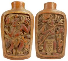 Mayan Culture Pottery: Flask shaped carved terracotta vessel of warriors in elaborate feathered costume on either side in low relief. Traces of brown, red, and orange.  600-900 AD