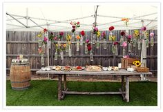 Wine bottle vases with flowers strung up with twine - neat decorating idea for outdoor party