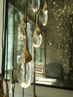Arctic Pear light fixture called Seed Cloud Installation. There are 114 solid cast bronze buds each housing a glass drop and illuminated by a single LED light... Like drops of water, bulbs of flowers... The organic form of the cast metal and the raw finish, in stark contract to the polished glass, beautiful!!