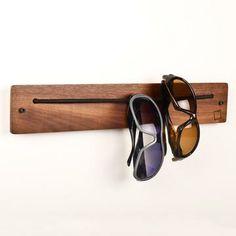 Para organizar os óculos, deixá-los sempre à mão e   manter o estilo, uma sugestão de algo simples e eficiente:  Uma pequena prancha, vazada nas pontas e acrescida de um elástico. :)