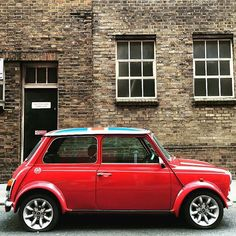 A red vintage Mini in London's Clerkenwell with a flag on top.