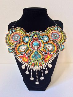 A beaded bib necklace with turquoise and rhinestone accents. Hundreds of colorful glass seed beads, silver metal and brass beads are hand-beaded