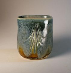 Square top with carved patterns on sides. Love the effect of the glaze.