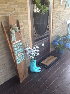 old wooden ironing board I painted a porch saying on it and added a burlap chevron bow:)