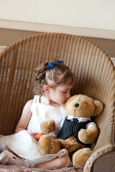 A flower girl and her dressed up bear.