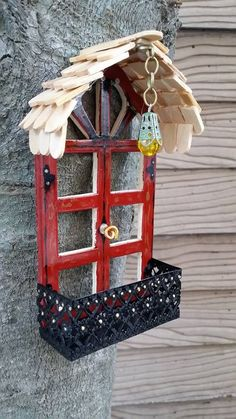 Fairy Garden Balcony with Hanging Lantern for Tree. The roof is made of popsicle stick ends glued together. The hanging lantern is a piece of jewelry chain, a green bead cap, and a plastic yellow bead. The door is a pre-cut dollhouse window that I just painted. The handle is a piece of gold floral wire. And the balcony is a piece of decorative tin ribbon spray painted black.