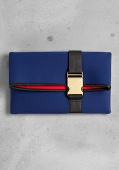Made from scuba fabric with a lightly padded feel, this clutch's clever design folds over itself to form a flap front, with the contrasting lining doubling as a standout front stripe. Hidden front pocket and gold metal snap-lock buckle on a black strap. Dimensions: 29 x 18 x 3 cm.
